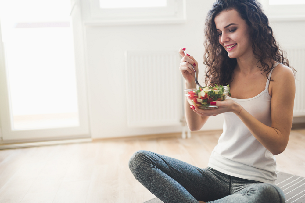 Image of young woman eating a salad