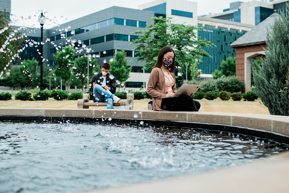 woman and man sitting at fountain with mask on