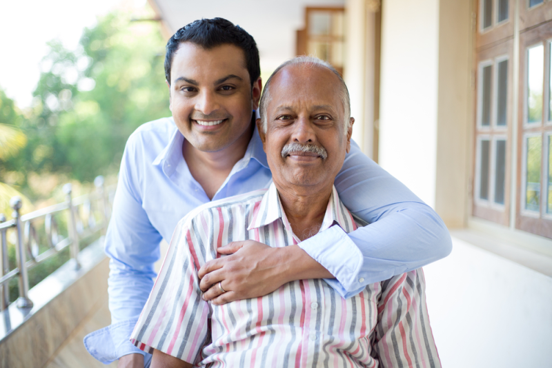 A younger male, smiling, with his arm around an elderly man