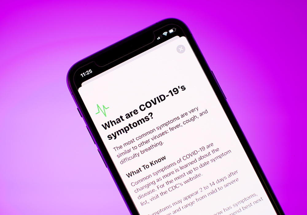 "Phone with article titled ""What are COVID-19's symptoms"" directing people to the CDC's site"